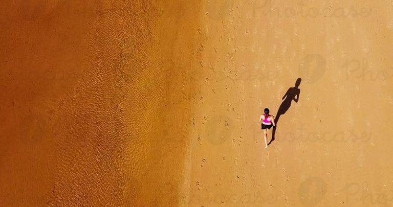 une femme qui court sur la plage avec un bracelet oeil de tigre